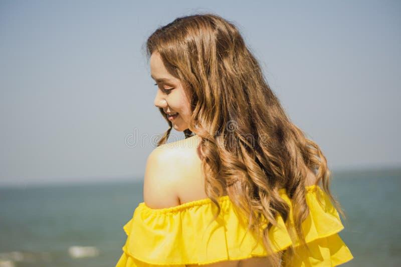 Pelo largo de la muchacha asiática del retrato, blanco del bikini postura feliz bicolor y amarillo, derecho del poste por el mar, fotografía de archivo libre de regalías
