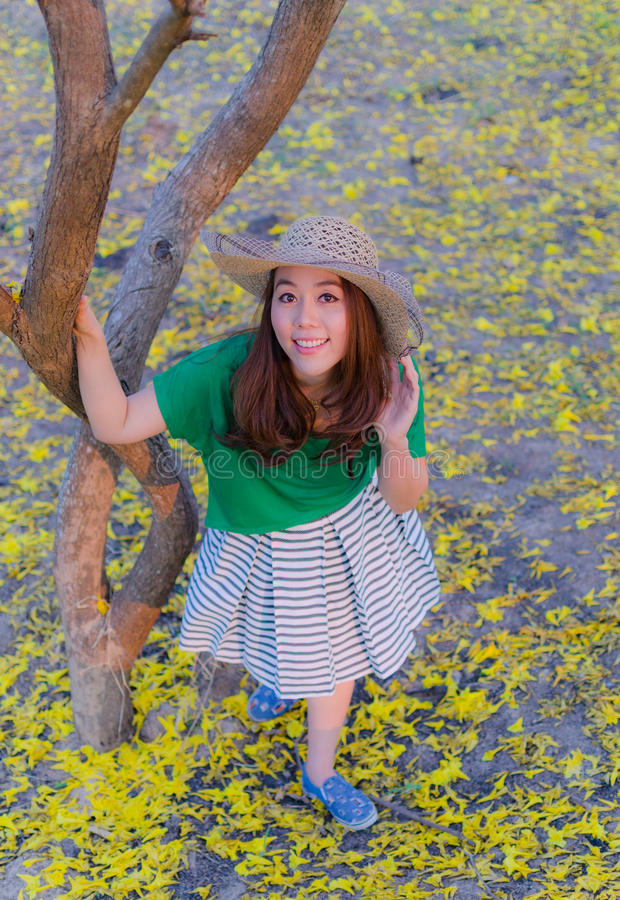 Pelo largo de la mujer hermosa con las flores amarillas en el jardín imagen de archivo