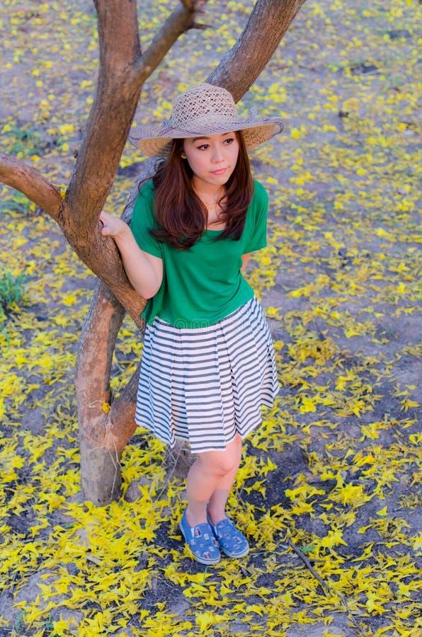 Pelo largo de la mujer hermosa con las flores amarillas en el jardín foto de archivo libre de regalías