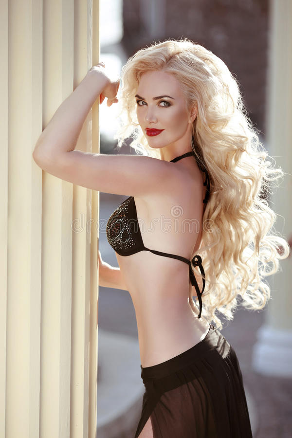 Pelo ondulado largo Modelo atractivo hermoso de la mujer en posin negro del bikini fotos de archivo libres de regalías