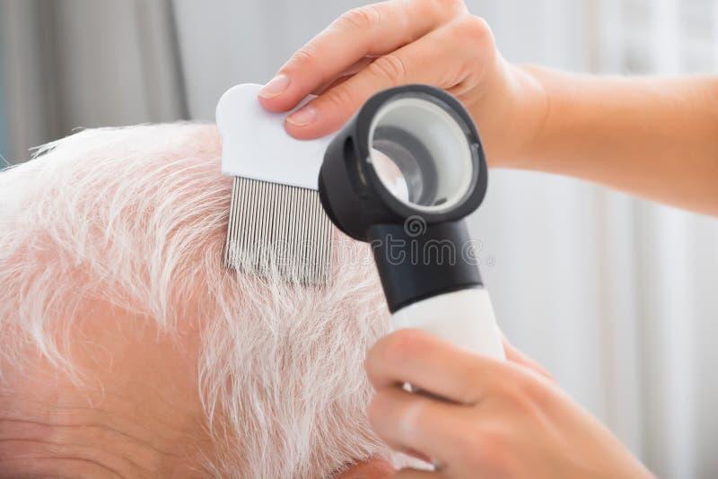Pelo paciente del ` s del doctor Doing Treatment Of foto de archivo