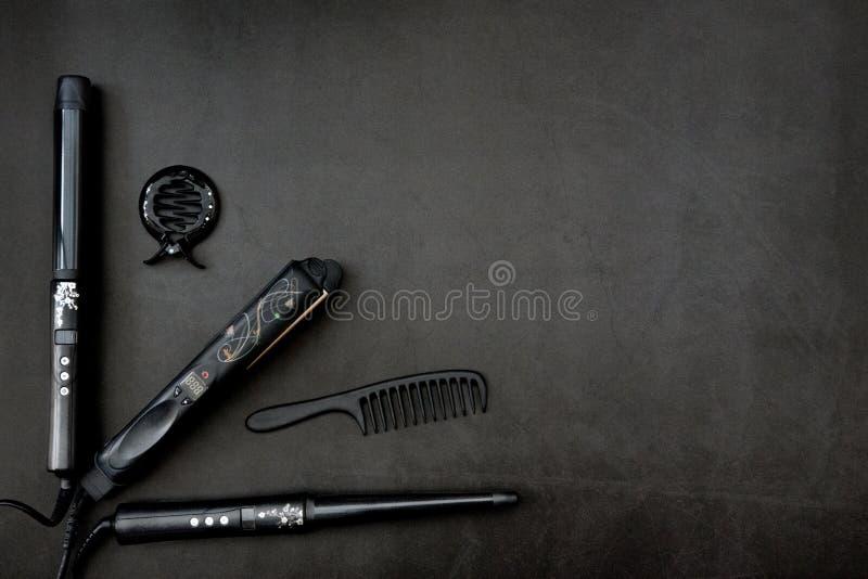 Pelo que diseña los accesorios en fondo negro, gris foto de archivo