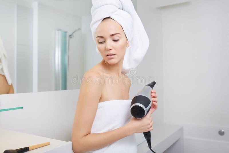 Pelo que hace el brushing de la mujer joven en cuarto de baño foto de archivo