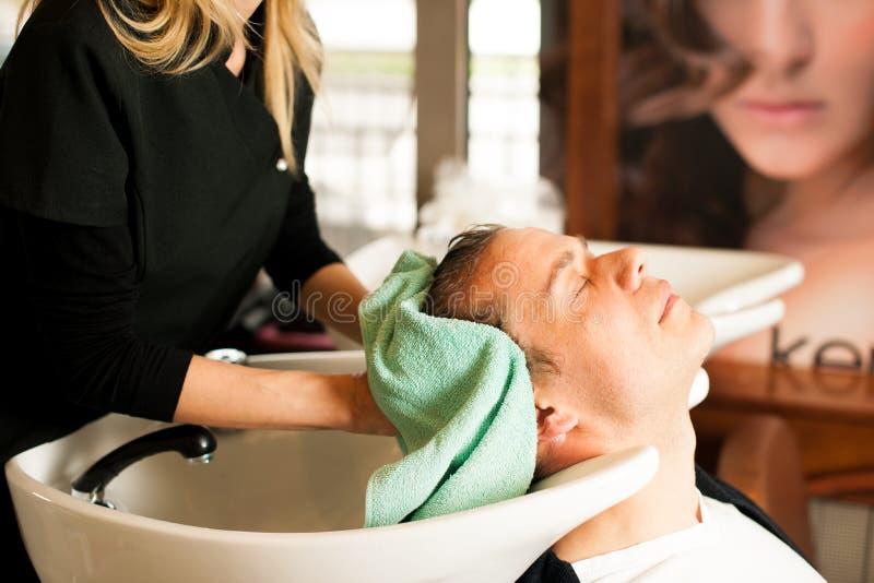 Pelo que se lava del peluquero de sexo femenino del cliente sonriente del hombre en la belleza fotografía de archivo