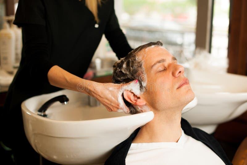 Pelo que se lava del peluquero de sexo femenino del cliente sonriente del hombre en la belleza fotos de archivo