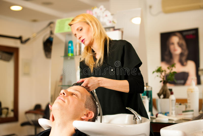 Pelo que se lava del peluquero de sexo femenino del cliente sonriente del hombre en la belleza imagen de archivo