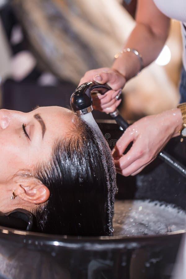 Pelo que se lava en un salón de la peluquería, muchacha caucásica joven imagen de archivo