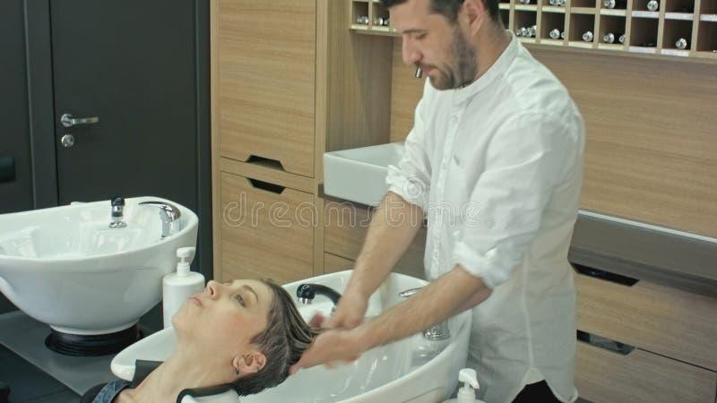 Pelo que se lava en un salón de la peluquería, muchacha caucásica joven foto de archivo libre de regalías