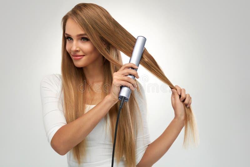 Pelo recto Mujer hermosa que plancha el pelo rubio largo foto de archivo