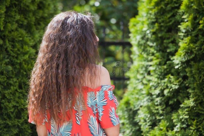 Pelo rizado en la calle, fondo Retrato ascendente cercano de una mujer hermosa joven con el pelo rizado moreno largo que presenta foto de archivo libre de regalías