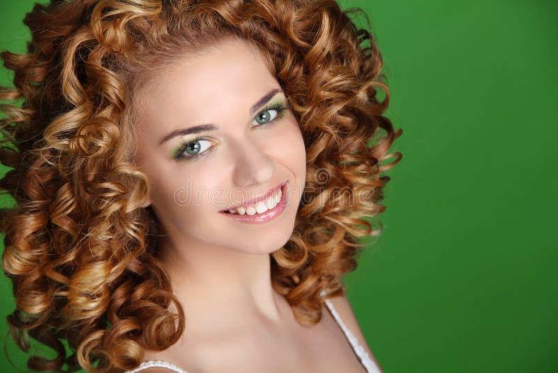 Pelo rizado. Retrato sonriente atractivo de la mujer foto de archivo