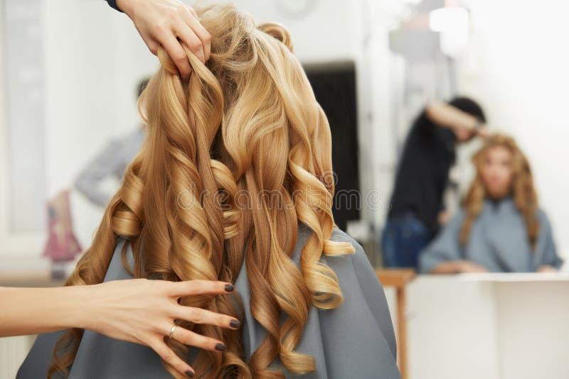Pelo rizado rubio Peluquero que hace el peinado para la mujer joven i imagenes de archivo