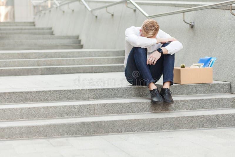 Pelo rojo infeliz y localización barbuda del hombre de negocios con la cartulina, agujereando la cabeza y sintiendo triste y el g foto de archivo libre de regalías