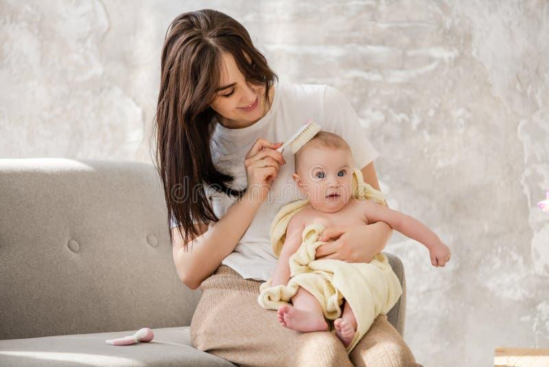 Pelo suave sonriente del bebé del cepillo de la madre foto de archivo libre de regalías