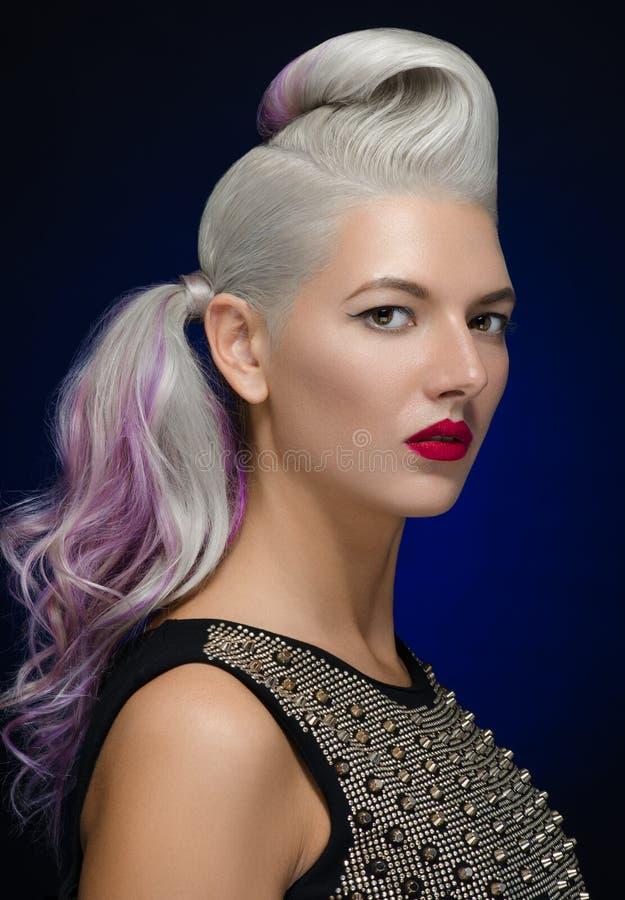 Pelo y tema del maquillaje: mujer rubia joven hermosa con el pelo creativo que diseña con los labios rojos en un fondo azul marin imagenes de archivo