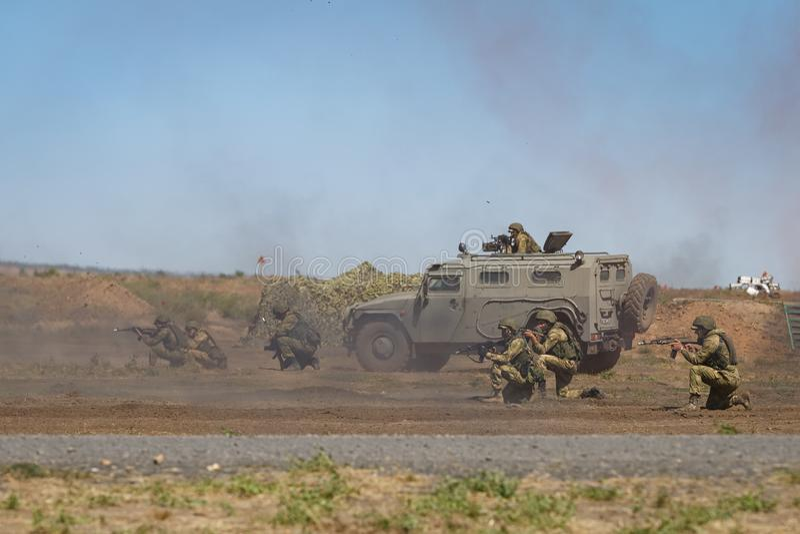 Pelotão de soldados armados junto com um carro blindado no campo de batalha para defender suas posições imagem de stock