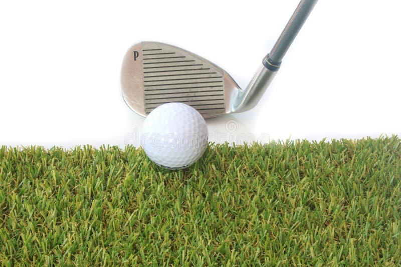Pelota de golf aislada en hierba verde sobre el fondo blanco imagen de archivo