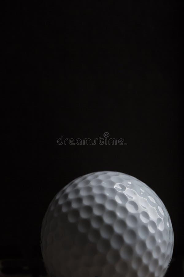 Pelota de golf aislada en un fondo negro con área de la copia imagen de archivo libre de regalías