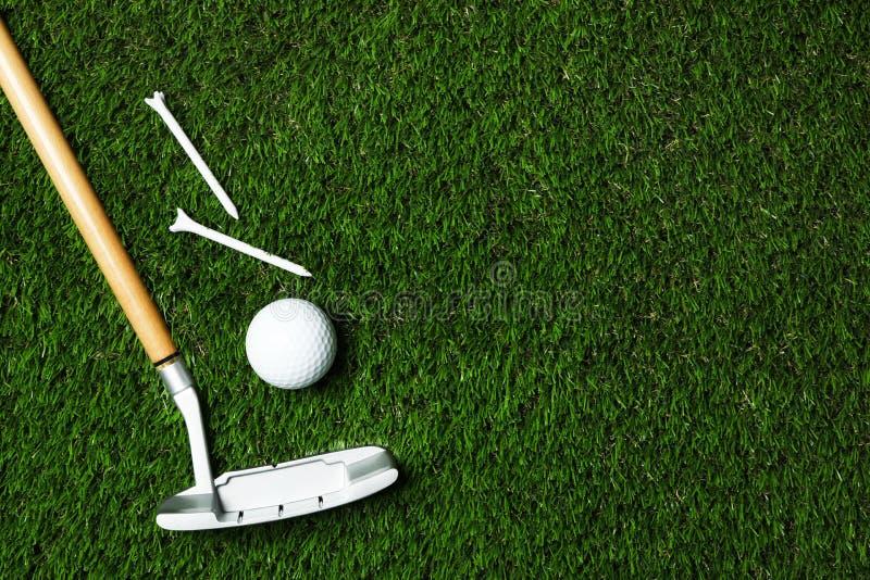 Pelota de golf, club y camisetas en la hierba artificial, visión superior imagen de archivo