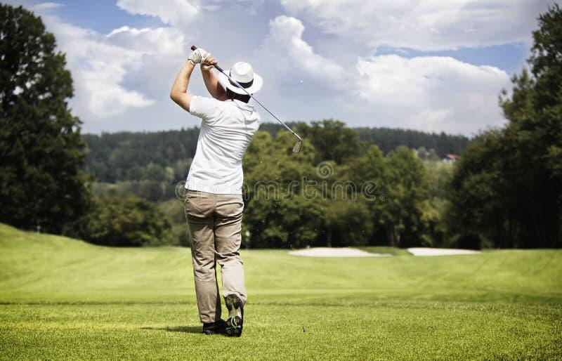 Pelota de golf del hombre que junta con te-apagado. imagenes de archivo