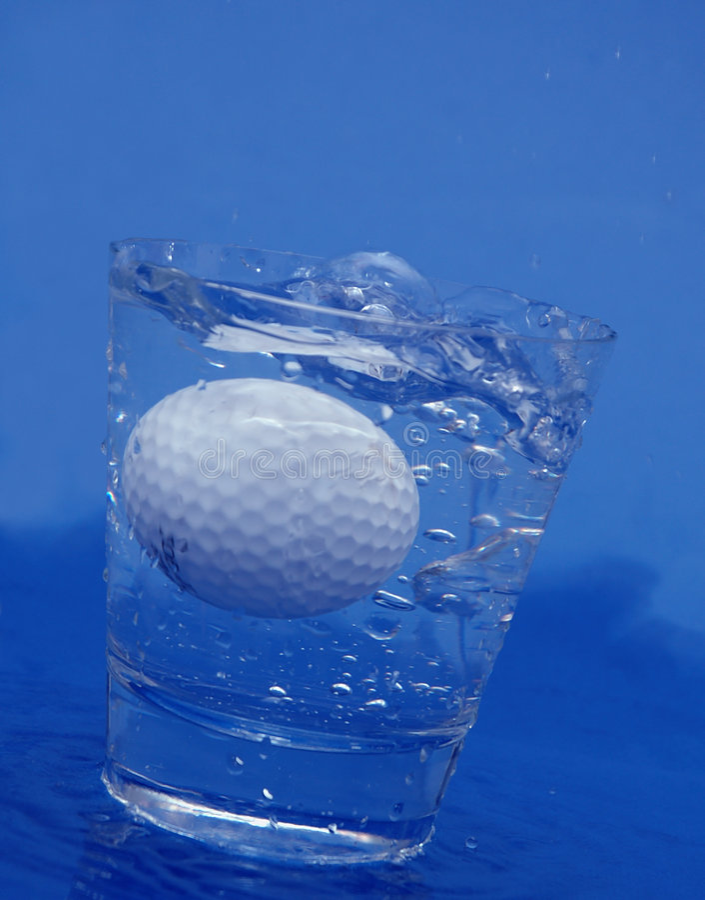 Pelota de golf en agua foto de archivo
