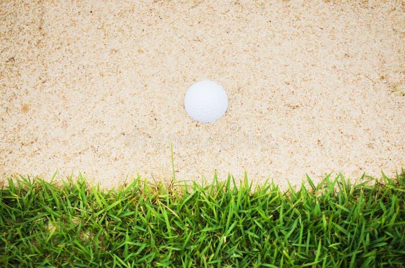 Pelota de golf en arena imagen de archivo
