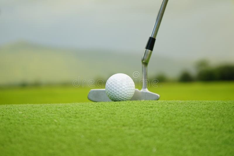 Pelota de golf en camiseta en campo de golf hermoso en el fondo de la puesta del sol fotografía de archivo libre de regalías