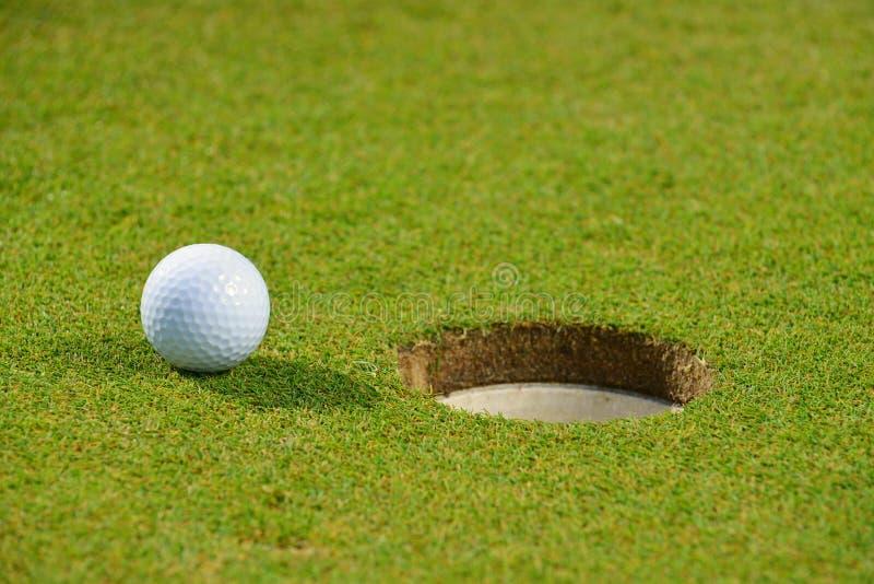Pelota de golf en el labio de la taza fotos de archivo