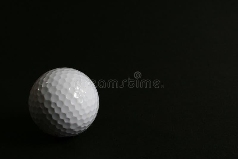 Pelota de golf en fondo negro fotos de archivo