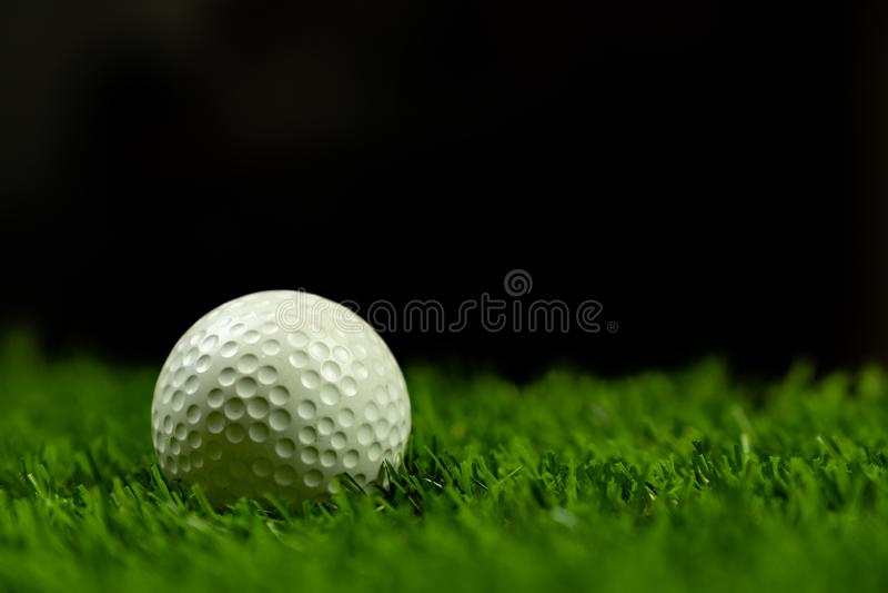 Pelota de golf en hierba en fondo negro imagen de archivo libre de regalías