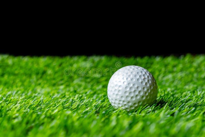 Pelota de golf en hierba en fondo negro fotografía de archivo