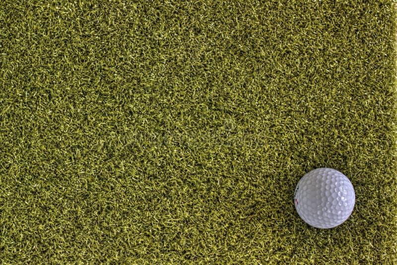 Pelota de golf en la tierra trasera verde imagenes de archivo