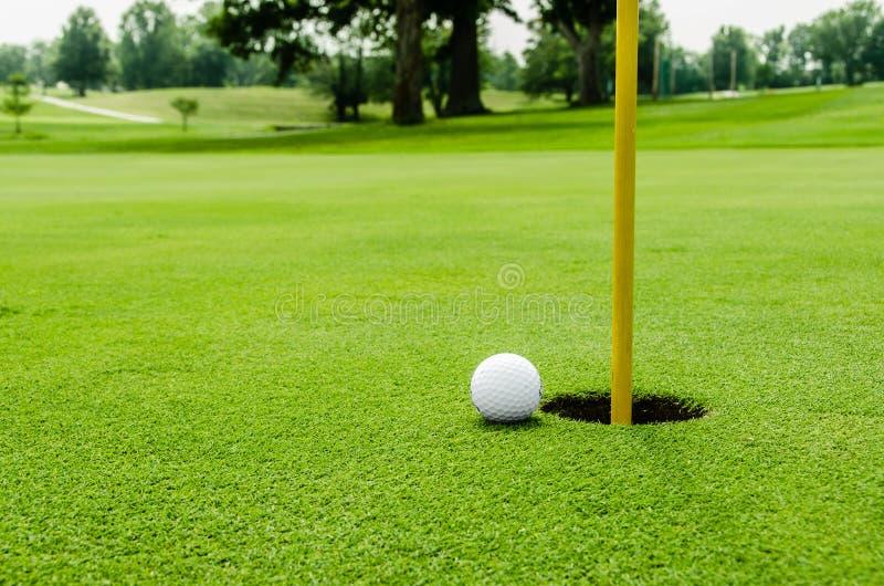 Pelota de golf en lipon el verde foto de archivo