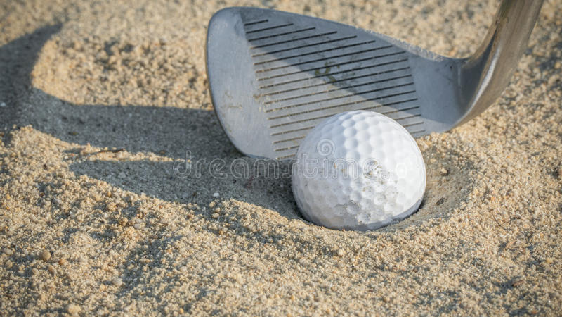 Pelota de golf en trampa de arena con la cuña de cabeceo fotos de archivo