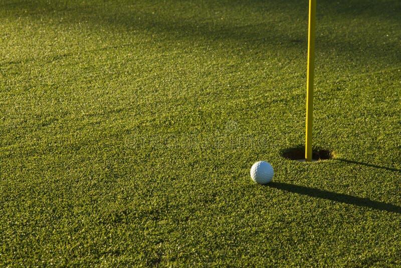 Pelota de golf en verde en la salida del sol imagenes de archivo