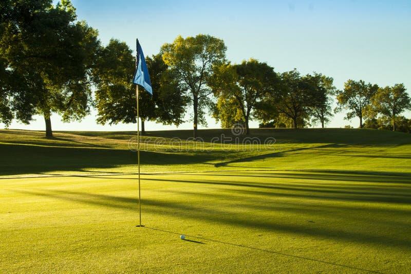 Pelota de golf en verde en la salida del sol foto de archivo