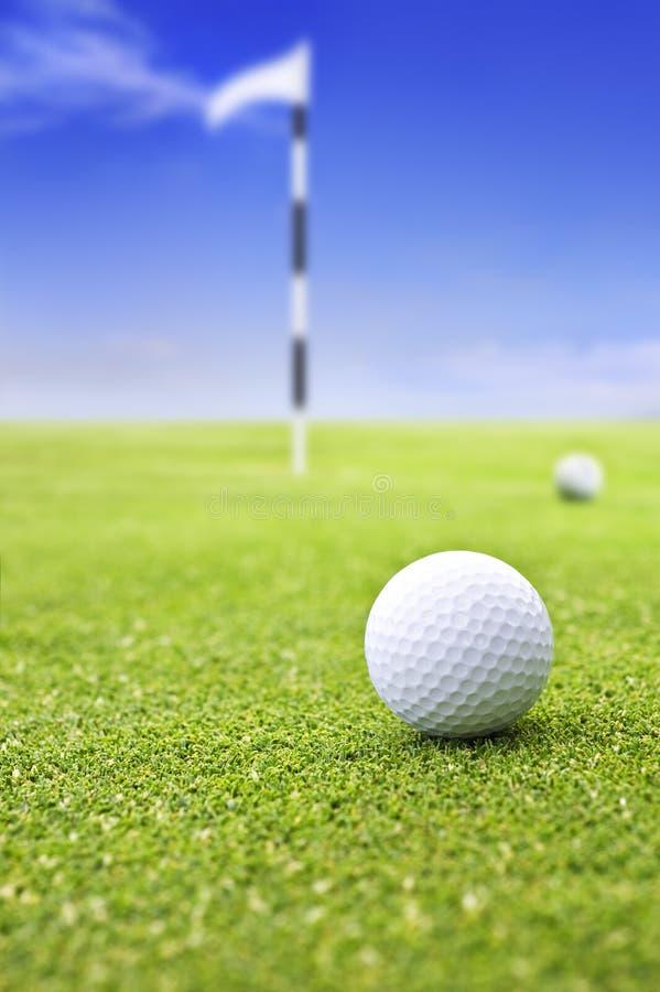 Pelota de golf en verde que pone imagen de archivo libre de regalías
