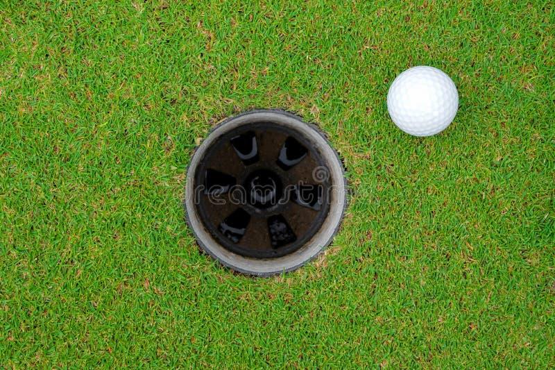 Pelota de golf y agujero del golf en hierba verde fotografía de archivo