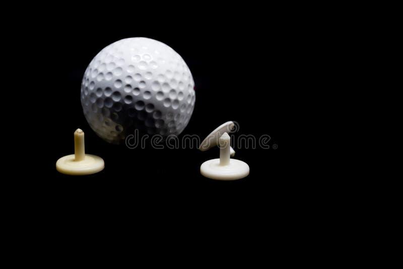 Pelota de golf y camiseta en fondo negro imágenes de archivo libres de regalías