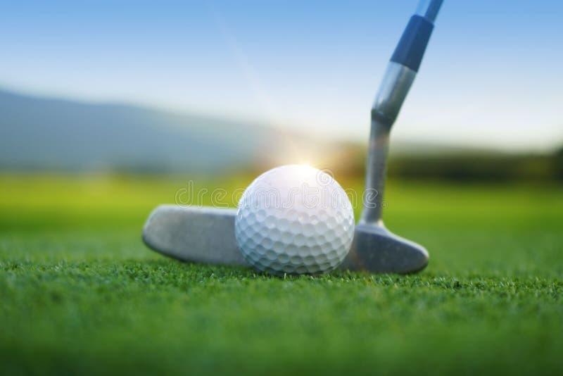 Pelota de golf y club de golf en campo de golf hermoso en el backg de la puesta del sol fotografía de archivo libre de regalías
