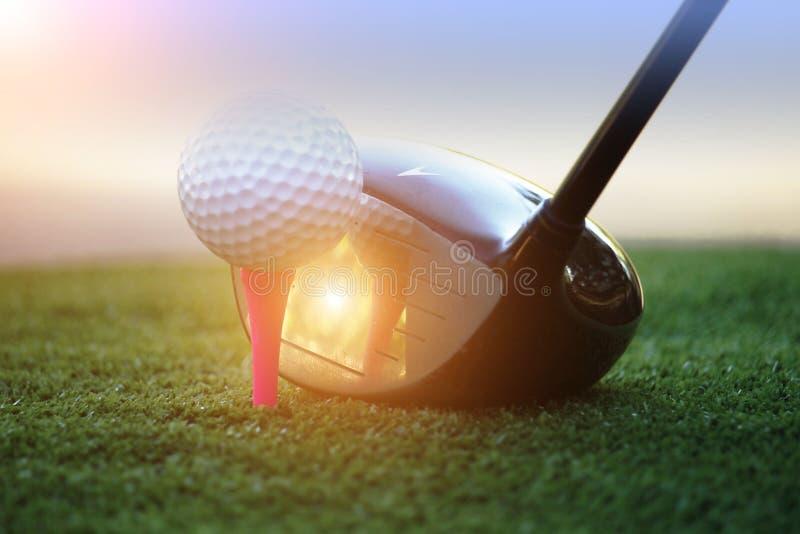 Pelota de golf y club de golf en el campo de golf hermoso de Asia en el fondo de la puesta del sol imagen de archivo