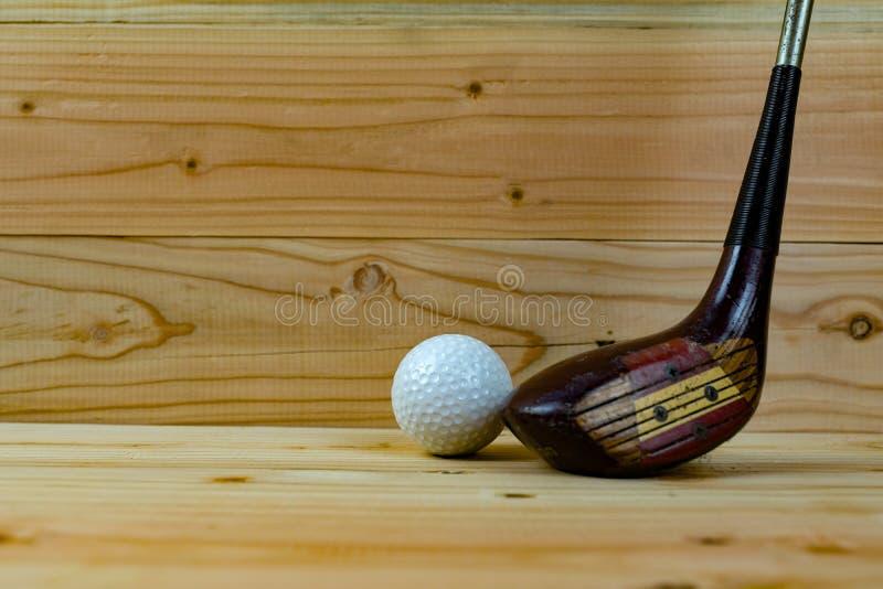 Pelota de golf y club de golf en el piso de madera fotos de archivo