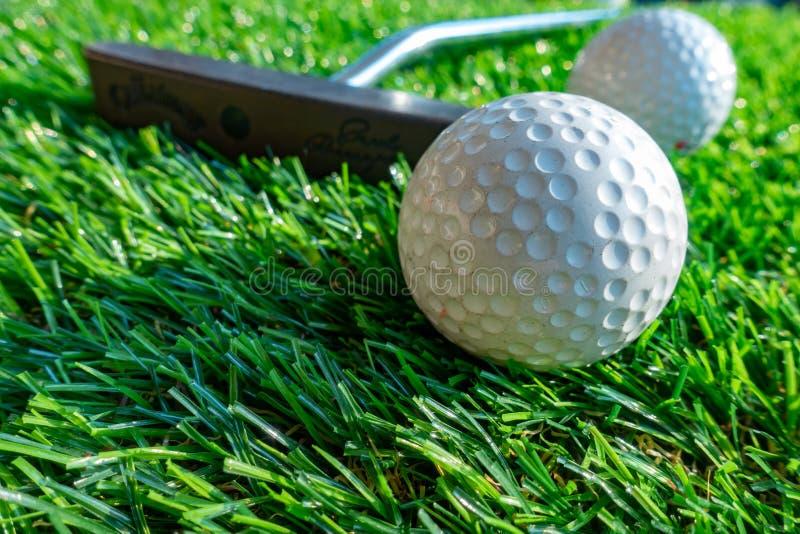 Pelota de golf y putter en hierba imagen de archivo