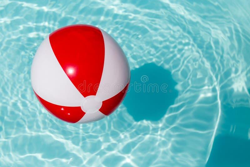 Pelota de playa roja y blanca en una piscina imagen de archivo