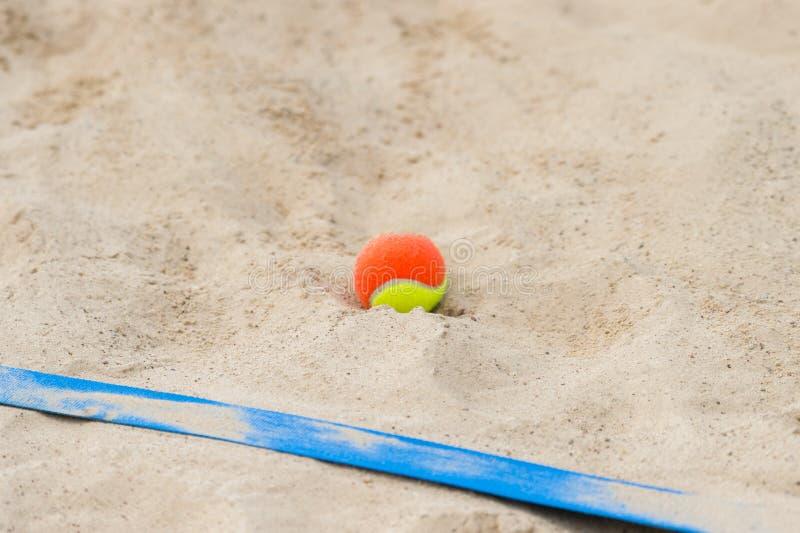 Pelota de tenis en la arena en el cierre de la playa para arriba fotografía de archivo libre de regalías