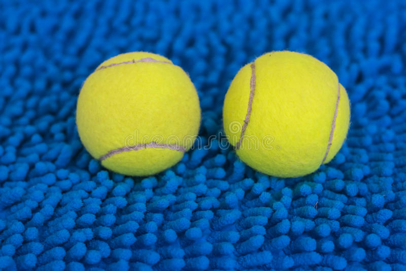 Pelota de tenis en la estera azul imagen de archivo