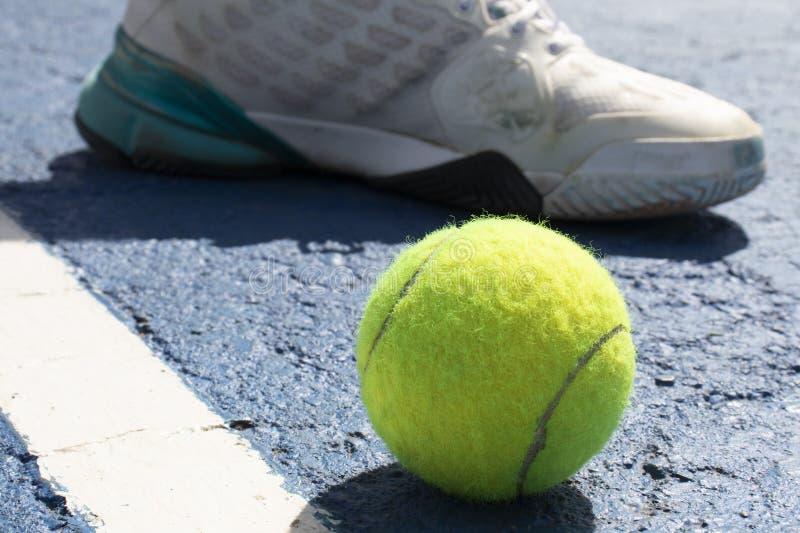 Pelota de tenis y zapatilla de deporte blanca imagen de archivo