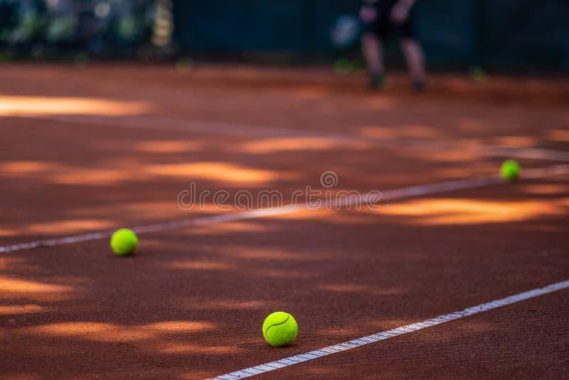 Pelotas de tenis en una corte en el primero plano Persona borrosa en imagen de archivo libre de regalías