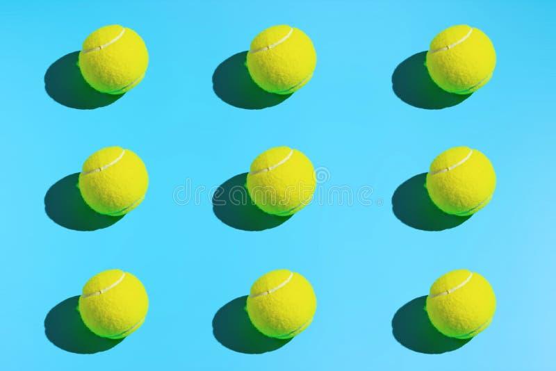 Pelotas de tenis simétricas en un fondo azul Se divierte el fondo fotos de archivo