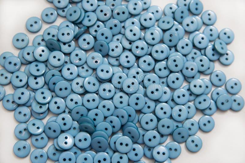 Pelotas plásticas plásticas dos botões dispersadas em um fundo branco fotografia de stock royalty free